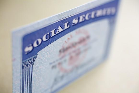 A Social Security card standing up on a table with the name and number blurred out.