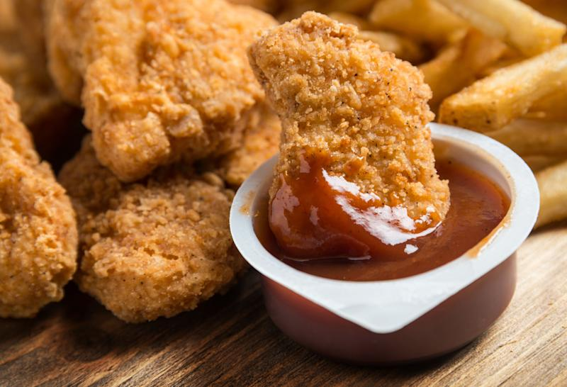 Chicken nuggets dipping in a BBQ sauce container and french fries