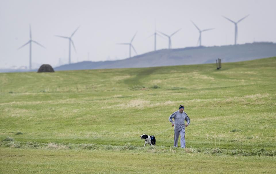 A man walking his dog near Whitehaven in Cumbria, where the proposed mine will be built (Photo: PA Images)
