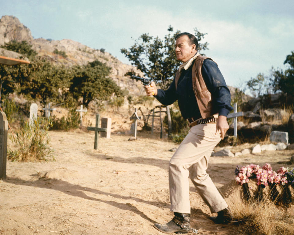 John Wayne (1907 - 1979), US actor wearing a tan leather waistcoat, a dark blue shirt and beige trousers, firing a pistol in a cemetery, circa 1960. (Photo by Silver Screen Collection/Getty Images)