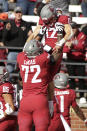 Washington State offensive lineman Abraham Lucas (72) lifts up wide receiver Joey Hobert (12) as they celebrate Hobert's touchdown during the second half of an NCAA college football game against Oregon State, Saturday, Oct. 9, 2021, in Pullman, Wash. Washington State won 31-24. (AP Photo/Young Kwak)
