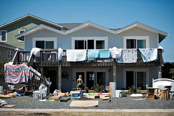 PHOTO: A boy walks in front of a home with items laid out to dry following the previous nights storm surge from Hurricane Isaias on Aug. 4, 2020, in Holden Beach, N.C. (Sean Rayford/Getty Images)