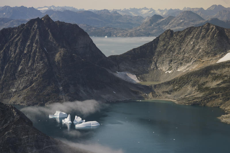 In this photo taken on Wednesday, Aug. 14, 2019, icebergs are photographed from the window of an airplane carrying NASA Scientists as they fly on a mission to track melting ice in eastern Greenland. Greenland has been melting faster in the last decade and this summer, it has seen two of the biggest melts on record since 2012. (AP Photo/Mstyslav Chernov)