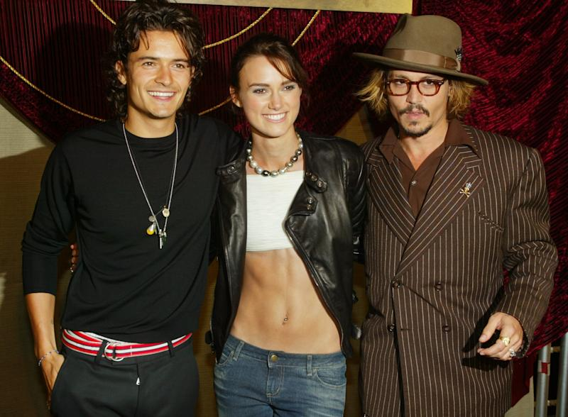 """The cast of the new film, """"The Pirates of the Caribbean The Curse of The Black Pearl,"""" (L-R) British actors Orlando Bloom and Keira Knightley along with star Johnny Depp, pose together at the film's premiere at Disneyland in Aneheim, California, June 28, 2003. This was the first premiere ever held at the theme park. The film opens July 9 in the United States. REUTERS/Fred Prouser FSP/HB"""