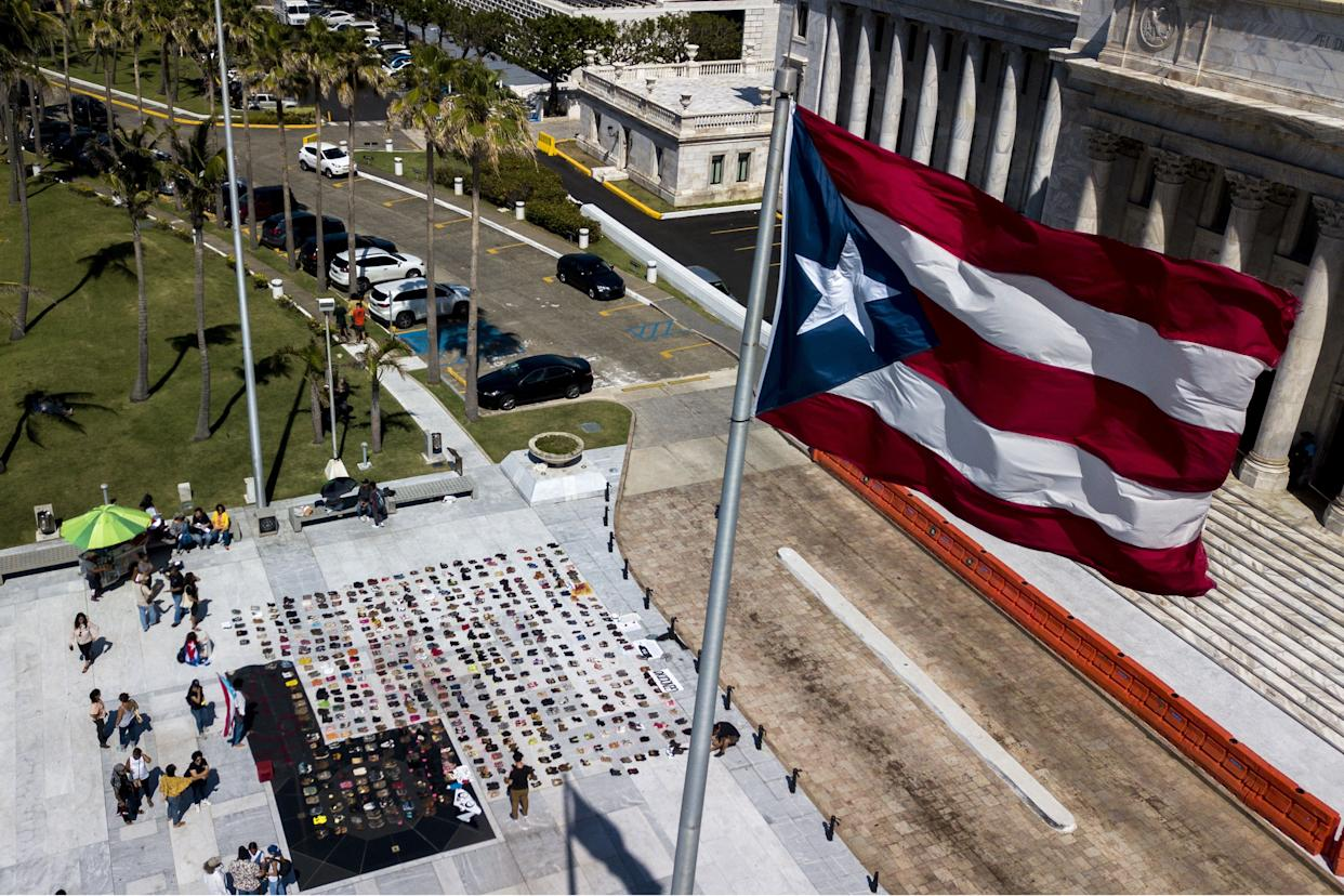 A Puerto Rican flag flies above empty pairs of shoes outside the island's Capitol building. (Photo: Bloomberg via Getty Images)