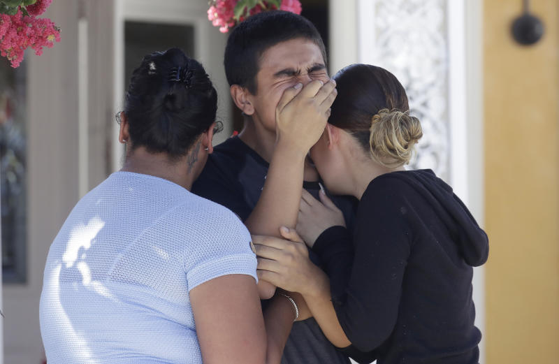 Joshua Guicho, 16, center, cries between his aunts Josephine Guicho, left, and Erica Guicho while being interviewed about the shooting death of his 6-year-old cousin Stephen Romero in San Jose, Calif., Monday, July 29, 2019. Romero is one of three young people who died when a gunman opened fire at a popular California food festival Sunday. (AP Photo/Jeff Chiu)
