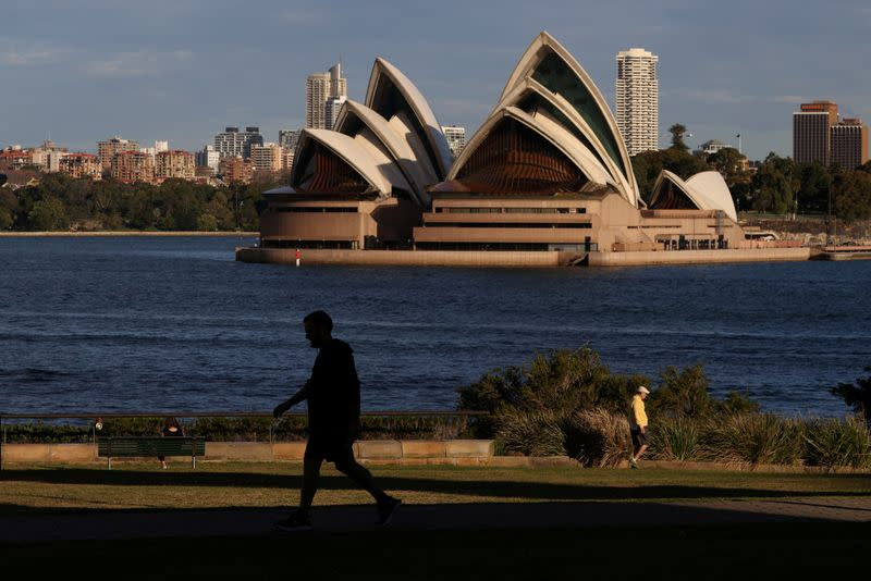 FILE PHOTO: People stroll through a park in front of the Sydney Opera House in Sydney