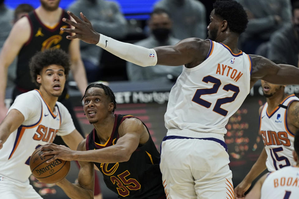 Cleveland Cavaliers' Isaac Okoro (35) drives to the basket against Phoenix Suns' Deandre Ayton (22) in the second half of an NBA basketball game, Tuesday, May 4, 2021, in Cleveland. (AP Photo/Tony Dejak)