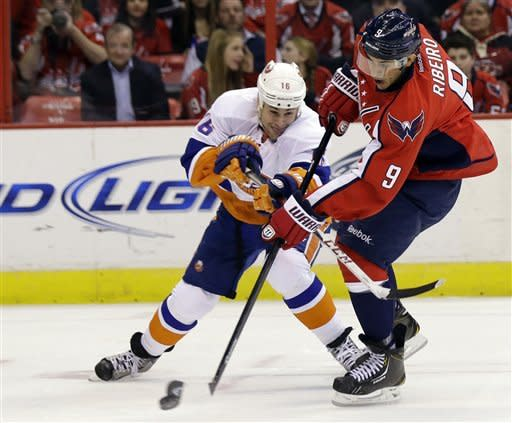Washington Capitals center Mike Ribeiro (9) shoots for a goal as New York Islanders center Marty Reasoner (16) defends during the second period of an NHL hockey game Tuesday, March 26, 2013, in Washington. (AP Photo/Alex Brandon)