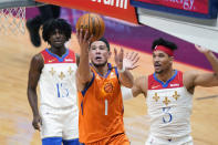 Phoenix Suns guard Devin Booker (1) drives to the basket in front of New Orleans Pelicans guard Josh Hart (3) and guard Kira Lewis Jr. (13) during the second half of an NBA basketball game in New Orleans, Friday, Feb. 19, 2021. (AP Photo/Gerald Herbert)