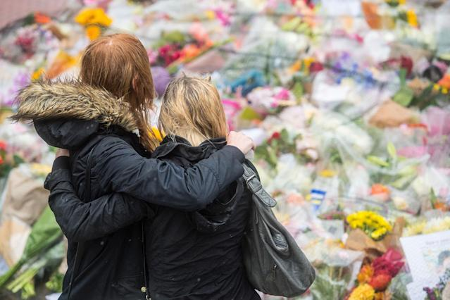 <p>Women comfort each other as they look at flowers laid near the scene of Saturday's terrorist attack, ahead of a minutes silence, on June 6, 2017 in London, England. (Photo: Carl Court/Getty Images) </p>