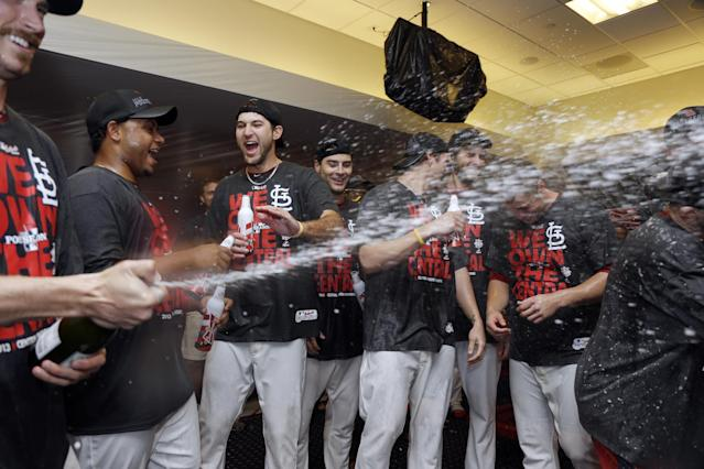 Members of the St. Louis Cardinals celebrate after a 7-0 win over the Chicago Cubs in a baseball game to clinch the NL Central title Friday, Sept. 27, 2013, in St. Louis. (AP Photo/Jeff Roberson)