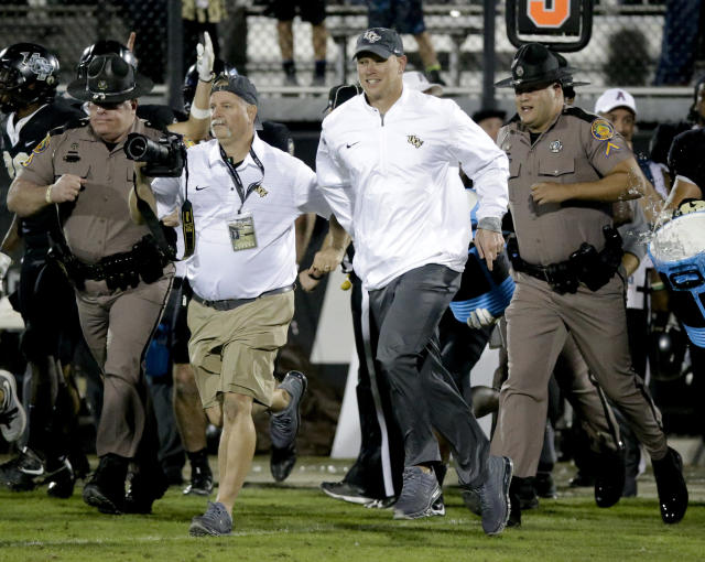 Central Florida coach Scott Frost (C) runs onto the field after the team defeated South Florida 49-42 in an NCAA college football game, Friday, Nov. 24, 2017, in Orlando, Fla. (AP Photo/John Raoux)