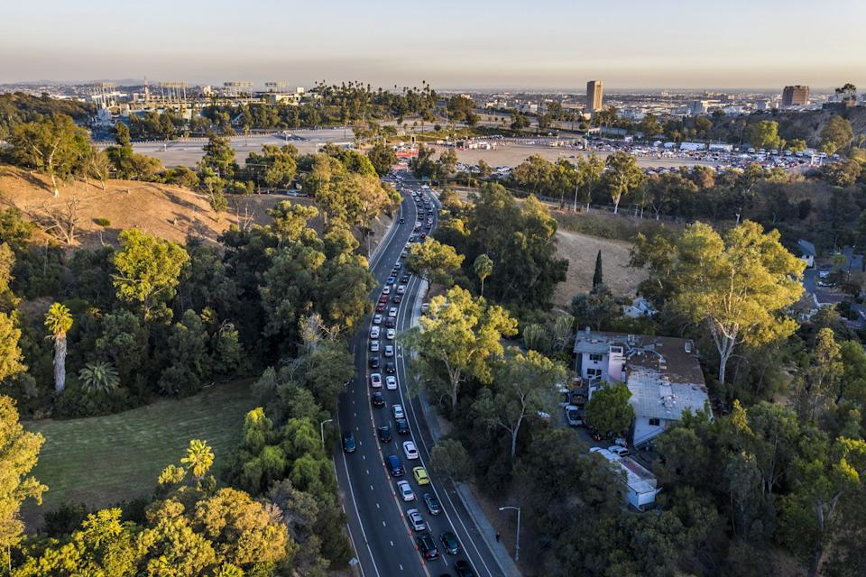 Two lanes packed with cars on the roadway leading to Dodger Stadium, lined with parkland and trees