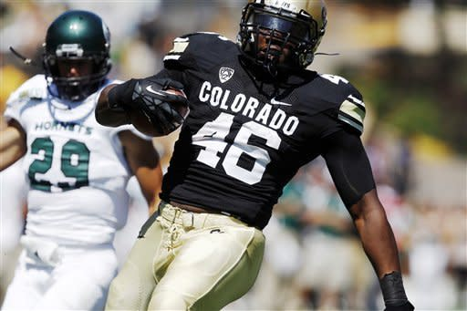 Colorado fullback Christian Powell celebrates as he scores a touchdown on a run past Sacramento State defensive back Robert Beale in the first quarter of an NCAA college football game in Boulder, Colo., Saturday, Sept. 8, 2012. (AP Photo/David Zalubowski)
