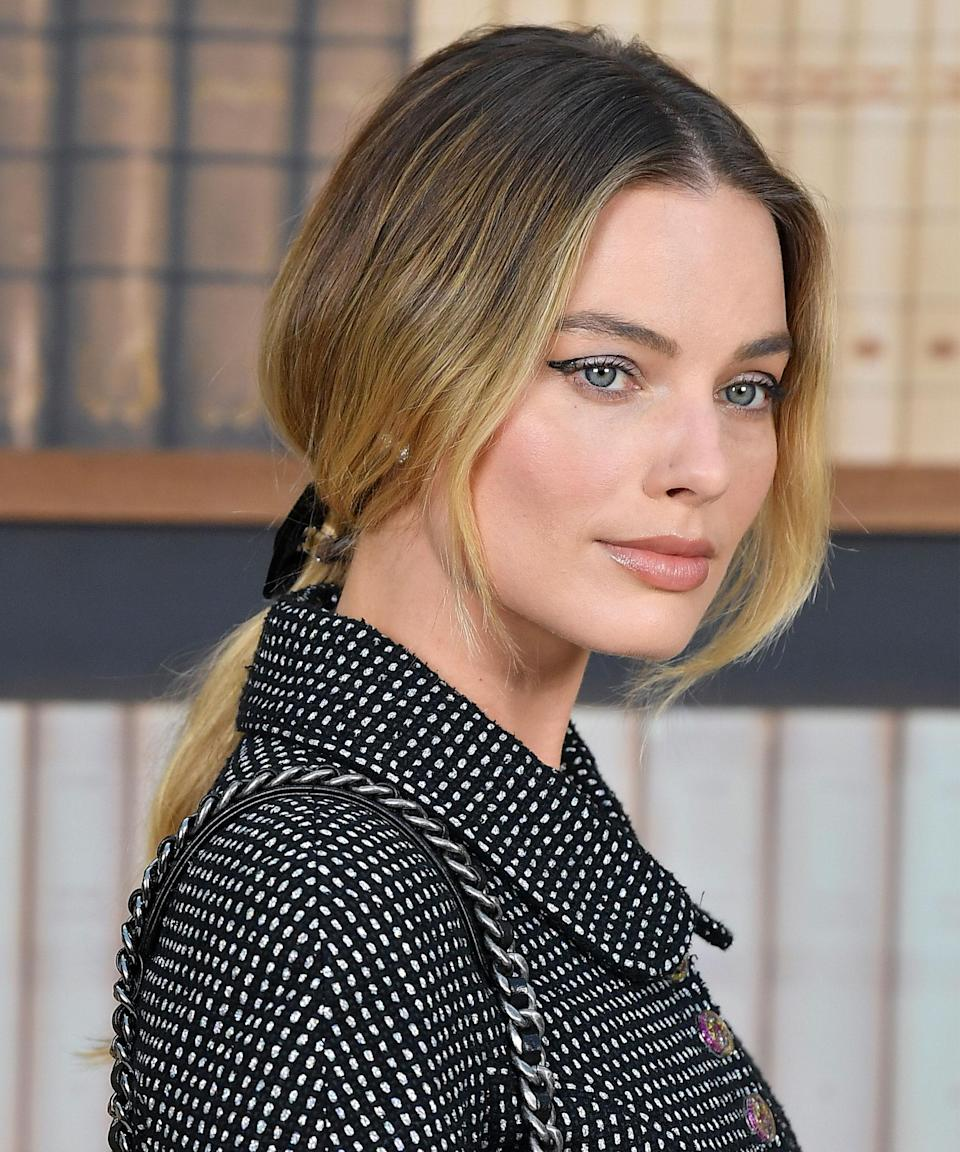 """<h3><strong>Undone Updo</strong></h3> <br><br>This summer, the <a href=""""https://www.refinery29.com/en-us/messy-updos"""" rel=""""nofollow noopener"""" target=""""_blank"""" data-ylk=""""slk:undone updo"""" class=""""link rapid-noclick-resp"""">undone updo</a> — both polished and piece-y at the same time — has proven to be the style <em>du jour</em> in Hollywood. Unsurprisingly, Robbie and Scarlett have nailed the vibe. Last season, Robbie was spotted in a low, ribbon-wrapped ponytail with soft, face-framing strands at the Chanel show during <a href=""""https://www.refinery29.com/en-us/summer-wedding-beauty-looks-couture-fashion-week"""" rel=""""nofollow noopener"""" target=""""_blank"""" data-ylk=""""slk:Haute Couture Fashion Week in Paris"""" class=""""link rapid-noclick-resp"""">Haute Couture Fashion Week in Paris</a>.<span class=""""copyright"""">Photo: Stephane Cardinale/Corbis/Getty Images. </span><br><br>"""