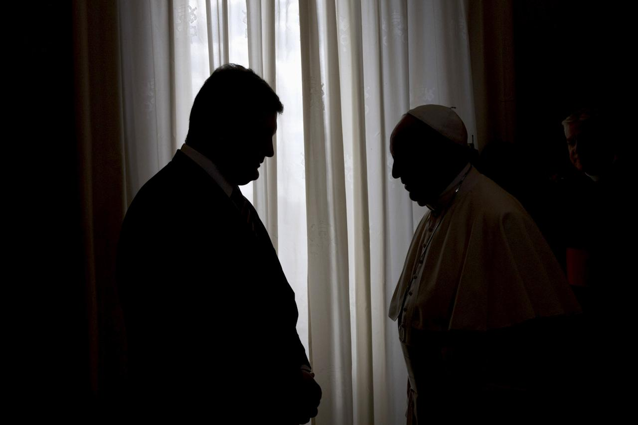 Pope Francis and Ukrainian President Petro Poroshenko (L) are silhouetted during a meeting at the Vatican November 20, 2015. REUTERS/Alessandra Tarantino/Pool      TPX IMAGES OF THE DAY