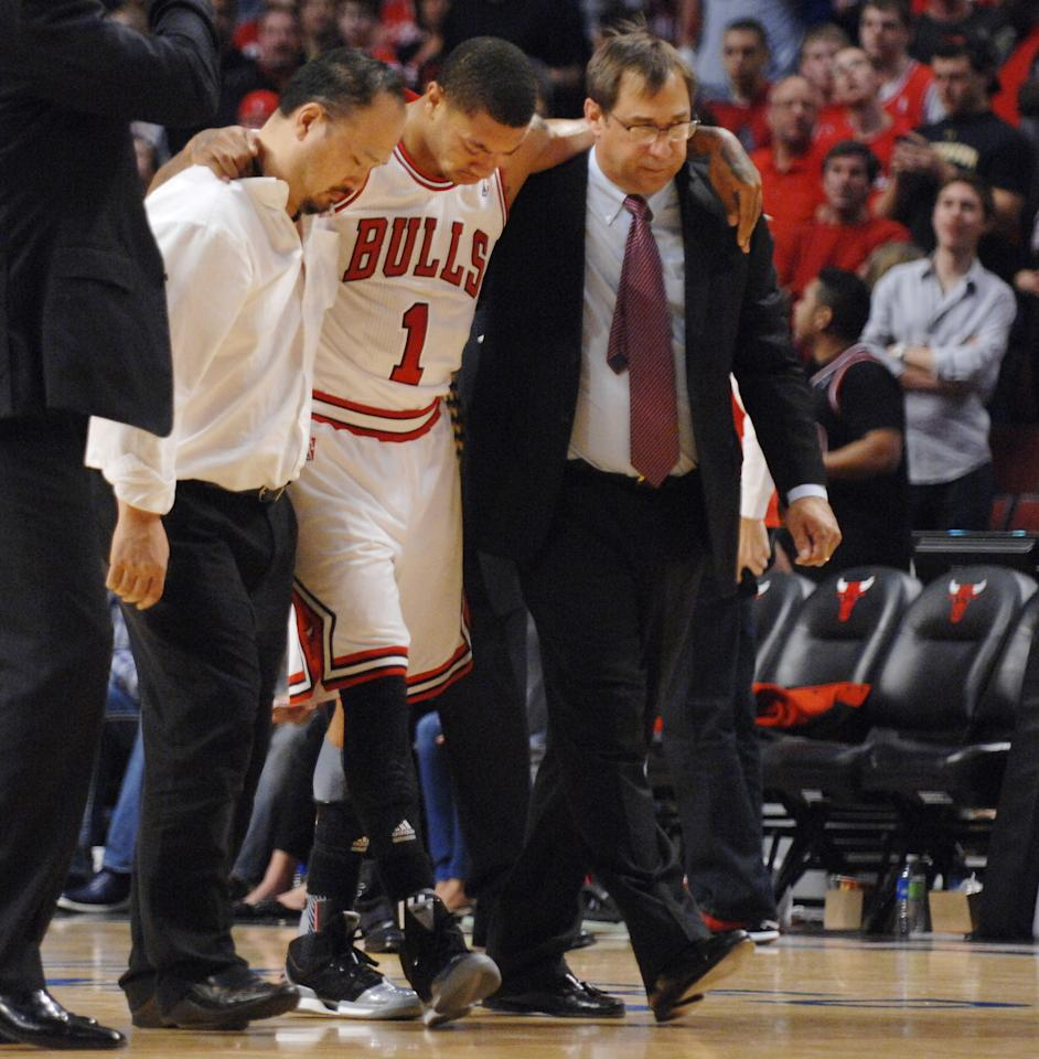Chicago Bulls point guard Derrick Rose is assisted off the court after injuring his leg in the fourth quarter of Game 1 in the first round of the NBA basketball playoffs against the Philadelphia 76ers in Chicago, Saturday, April 28, 2012. The Bulls won 103-91. (AP Photo/Daily Herald, John Starks) MANDATORY CREDIT; TV OUT; MAGS OUT