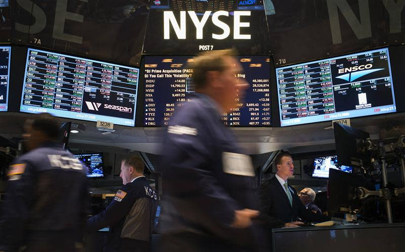 Traders work on the floor of the New York Stock Exchange after the opening bell