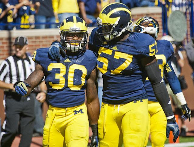 Michigan safety Thomas Gordon (30) and offensive lineman Patrick Kugler (57) celebrate after stopping Akron from scoring in the final seconds of an NCAA college football game in Ann Arbor, Mich., Saturday, Sept. 14, 2013. Michigan won 28-24. (AP Photo/Tony Ding)