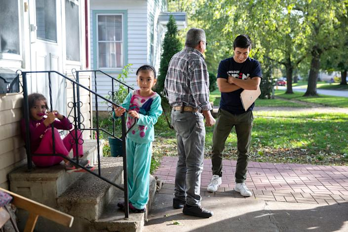 Camilo Haller, a field organizer for Joe Biden's campaign for president, talks to Ramon Medina-Rios, of Storm Lake, while knocking doors on Thursday afternoon, Oct. 17, 2019, in Storm Lake.