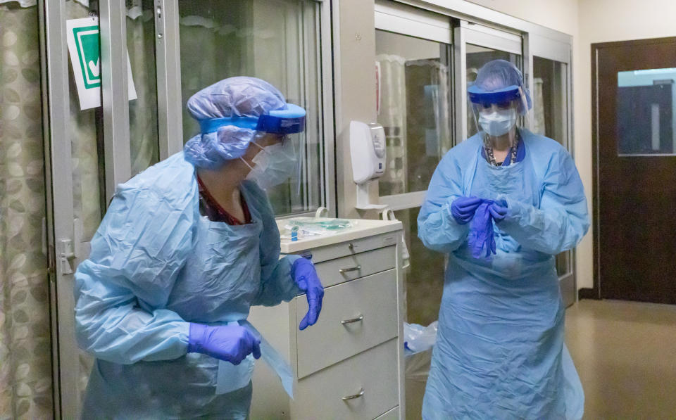 In this Thursday, Aug. 19, 2021, photo, nurses at Asante Three Rivers Medical Center wear specific personal protective equipment to safely work in the Critical Care Unit at Asante Three Rivers Medical Center in Grants Pass, Ore. Only essential staff are permitted in the zone, and those who enter a patient's room must don various articles of Personal Protective Equipment. The hospitalization rate of unvaccinated COVID-19 is breaking records and squeezing hospital capacity, with several running out of room to take more patients. (Mike Zacchino/KDRV via AP, Pool)