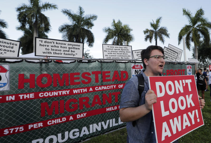 Kody Hersh holds a sign in front of a mock fence representing the Homestead Temporary Shelter for Unaccompanied Children, during a protest against the detention center, outside of the Knight Concert Hall at the Adrienne Arsht Center for the Performing Arts of Miami-Dade County, where a Democratic presidential debate is taking place, Wednesday, June 26, 2019, in Miami. (AP Photo/Lynne Sladky)