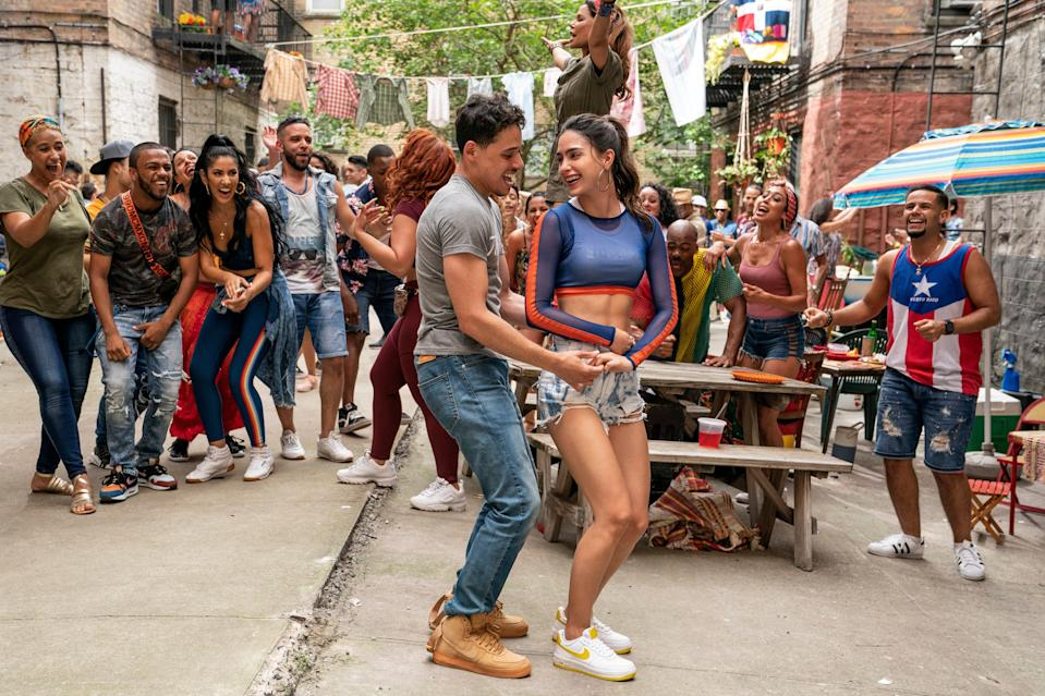 """Anthony Ramos (center, with Melissa Barrera) stars as a likable bodega owner in """"In the Heights,"""" a new adaptation of Lin-Manuel Miranda's Broadway musical."""""""