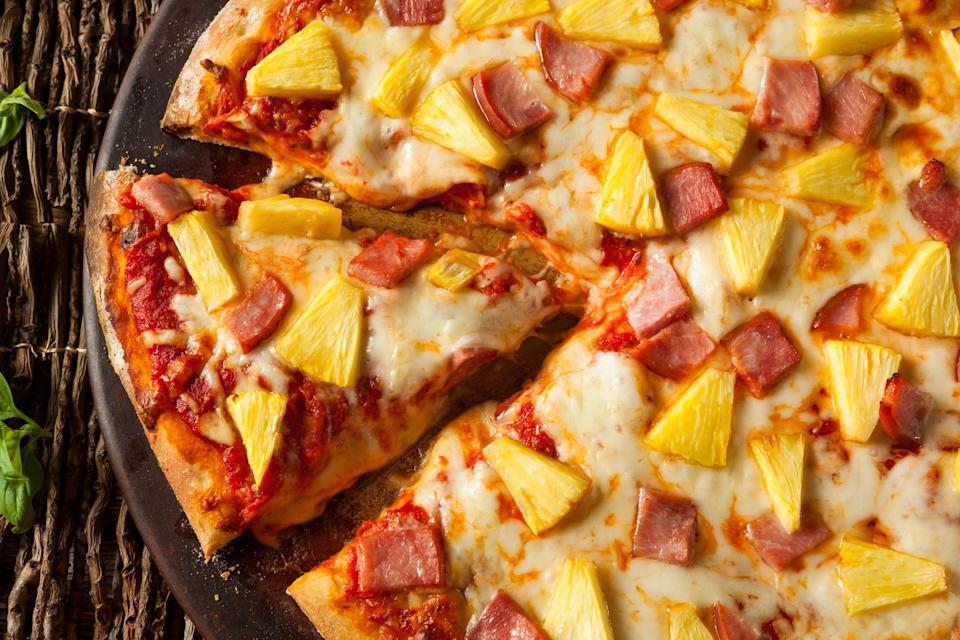 """<p>Everyone has their favorite pizza toppings. Some folks won't eat a slice without pepperoni, while others think that simple sauce and <a href=""""https://www.thedailymeal.com/travel/cheese-around-the-world-everyone-should-try?referrer=yahoo&category=beauty_food&include_utm=1&utm_medium=referral&utm_source=yahoo&utm_campaign=feed"""" rel=""""nofollow noopener"""" target=""""_blank"""" data-ylk=""""slk:quality cheese"""" class=""""link rapid-noclick-resp"""">quality cheese</a> is the way to go. But no pizza topping divides a group as much as pineapple. Some people like the sweet and salty contrast when it's paired with ham, while others think pineapple on pizza ruins this beloved dish.</p>"""