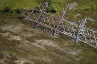 A twisted tower that carried crucial electrical feeder lines to the New Orleans metro area lies collapsed in the aftermath of Hurricane Ida in Bridge City, La., Wednesday, Sept. 1, 2021. Power out, high voltage lines on the ground, maybe weeks until electricity is restored in some places _ it's a distressingly familiar situation for Entergy Corp., Louisiana's largest electrical utility. Entergy is hardly alone. (AP Photo/Gerald Herbert)