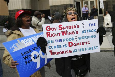 Resident Renla Session (R) holds a sign as she protests against Michigan Governor Rick Snyder's polices in front of the Federal Court House in Detroit, Michigan October 28, 2013. REUTERS/Rebecca Cook