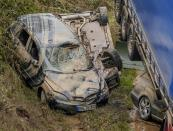 Two cars are next to a truck while another is under it on a road in Erftstadt, Germany, Saturday, July 17, 2021. Due to strong rain falls the small Erft river went over the banks causing massive damages. (AP Photo/Michael Probst)