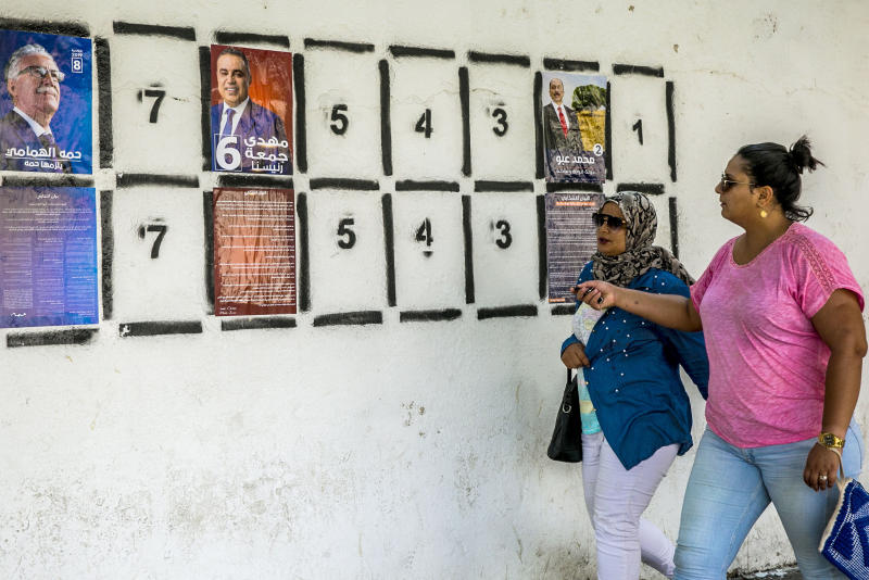Women walk past a wall of campaign posters in Tunis, Tunisia, Monday, Sept. 2, 2019.Tunisia's 26 presidential candidates have launched their campaigns in a political climate marked by uncertainty, money laundering allegations and worries about violent extremism. (AP Photo/Hassene Dridi)