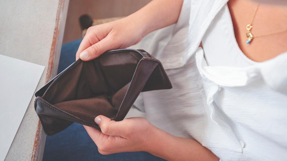 A woman opening an empty wallet.