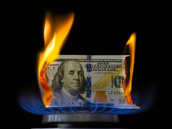 A hundred dollar bill on fire while atop a lit stove burner.