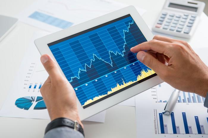 Two jacket-clad hands holding a tablet above a table full of charts and calculators. The right hand points to a chart on the screen, showing growth.