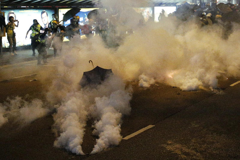 Protesters are engulfed by teargas during a confrontation with riot police in Hong Kong Sunday, July 21, 2019. Hong Kong police launched tear gas at protesters Sunday after a massive pro-democracy march continued late into the evening. The action was the latest confrontation between police and demonstrators who have taken to the streets to protest an extradition bill and call for electoral reforms in the Chinese territory. (Jacky Cheung/HK01 via AP)