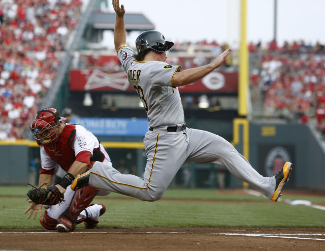 Pittsburgh Pirates' Travis Snider, right, scores at home past Cincinnati Reds catcher Devin Mesoraco, left, after a sacrifice fly by Russell Martin in the first inning of a baseball game, Saturday, July 12, 2014, in Cincinnati. (AP Photo/David Kohl)