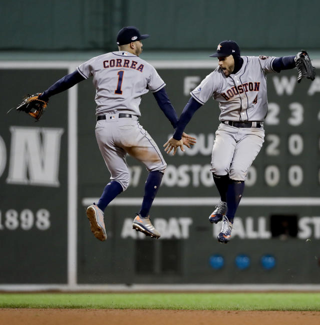Houston Astros center fielder George Springer, right, and shortstop Carlos Correa celebrate their win against the Boston Red Sox in Game 1 of a baseball American League Championship Series on Saturday, Oct. 13, 2018, in Boston. The Astros won 7-2. (AP Photo/David J. Phillip)