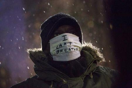 A man stands in falling snow following a news conference where members of Justice League NYC presented a list of demands at City Hall in New York December 10, 2014. REUTERS/Andrew Kelly