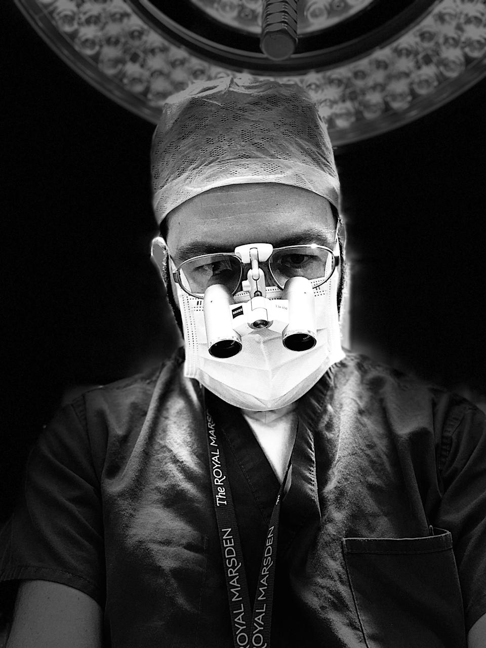 A black and white photo of a surgeon in an operating theatre. He is weirding a mask and glasses,