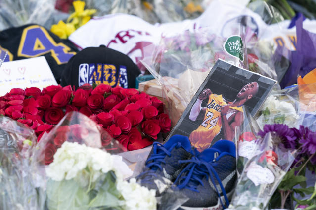 Flowers, jerseys and imagery are left in remembrance to Kobe Bryant at a small memorial at the entrance of the Bryant Gymnasium at Lower Merion High School, Monday, Jan. 27, 2020, in Wynnewood, Pa. Bryant, the 18-time NBA All-Star who won five championships and became one of the greatest basketball players of his generation during a 20-year career with the Los Angeles Lakers, died in a helicopter crash Sunday, Jan. 26. (AP Photo/Chris Szagola)