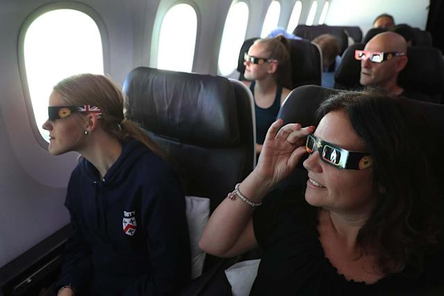 <p>Nicola James, 49, with her twin 18 year old daughters Holly (front left) and Grace watch the start of the solar eclipse while flying over the United States on board Virgin Atlantic Boeing 787 Dreamliner flight check VS5 from London's Heathrow airport to Miami. (Photo: Owen Humphreys/PA Images via Getty Images) </p>