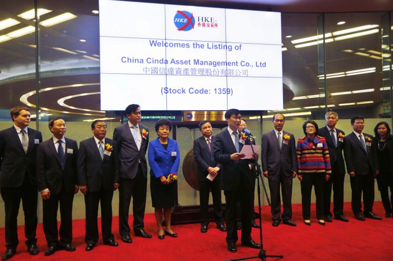 China Cinda Asset Management Chairman Hou Jianhang, center, speaks during the company listing ceremony at the Hong Kong Stock Exchange, Thursday, Dec. 12, 2013. A Chinese bad-debt management company's shares are soaring in their Hong Kong debut, highlighting strong investor appetite for a business that will flourish if the world's No. 2 economy stumbles. China Cinda Asset Management Co.'s shares jumped as much as 23 percent after they started trading Thursday. (AP Photo/Kin Cheung)