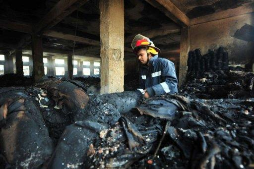 A Bangladeshi fire-man examines burnt materials after a fire in the nine-storey Tazreen Fashion plant in Savar