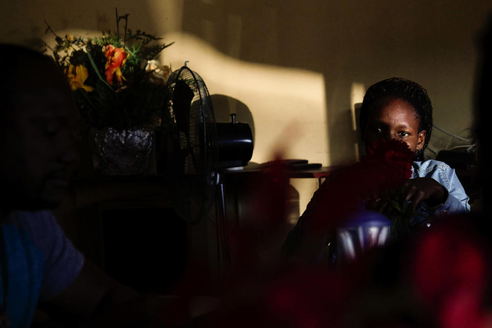 A woman from Haiti sits in a Haitian restaurant, Monday, Sept. 20, 2021, in Tijuana, Mexico. Many Haitians have established at least temporary legal status in Mexico, Brazil and elsewhere. (AP Photo/Gregory Bull)