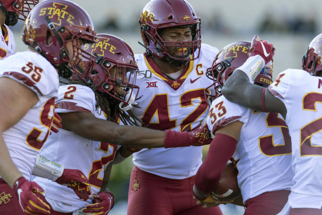 Iowa State wide defensive back Datrone Young (2) and linebacker Marcel Spears Jr. (42) celebrate with defensive back Braxton Lewis (33) after he recovered a fumble during the first half of an NCAA college football game against West Virginia, Saturday, Oct. 12, 2019, in Morgantown, W.Va. (AP Photo/Raymond Thompson)