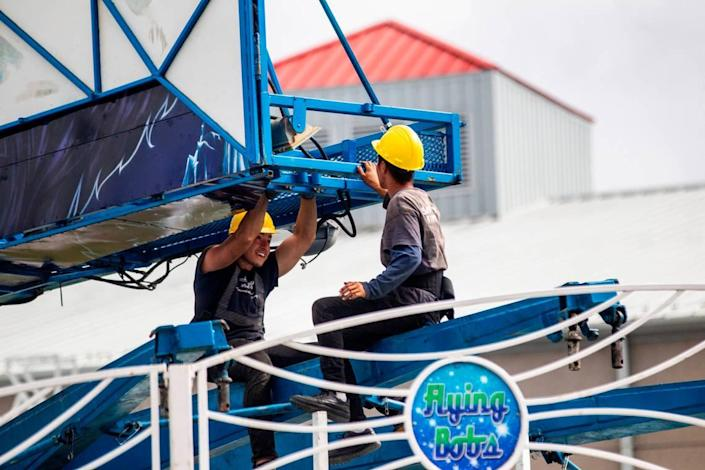 Workers assemble the Flying Bobs ride Tuesday, Oct. 12, 2021 at the NC State Fair in Raleigh. The North Carolina fair opens on Thursday and inspectors with the labor department must insure nearly 100 rides meet safety standards.