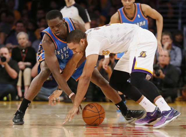 Oklahoma City Thunder point guard Reggie Jackson, left, and Los Angeles Lakers small forward Xavier Henry reach for a loose ball during the first half of an NBA basketball game in Los Angeles, Sunday, March 9, 2014. (AP Photo/Danny Moloshok)