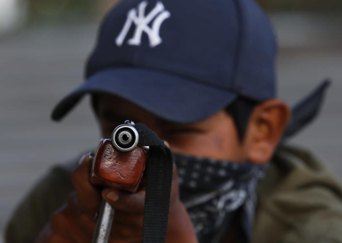 Luis Gustavo Morales, the 15-year-old son of a community policeman, practices his aim with a fake weapon during a display set up for the media to attract the federal government's attention to the dangers of organized crime which his town negotiates daily in Ayahualtempa, Guerrero state, Mexico, Wednesday, April 28, 2021. Luis Gustavo's father Luis Morales said that at first it made him sad to train his son to defend the town, but now he's proud of him because he will know how. (AP Photo/Marco Ugarte)